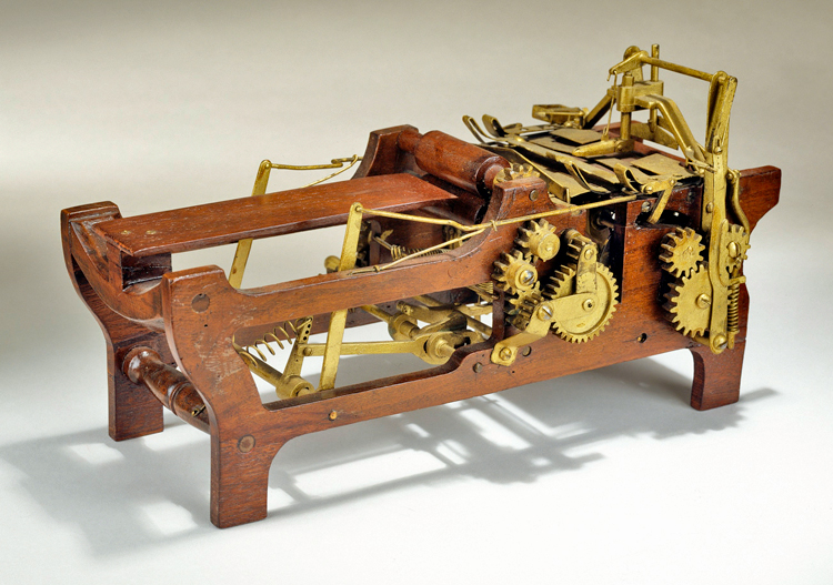 Margaret Knight's patent model for an improved paper bag making machine shows 2 sets of 3 gears attached by articulated arms and springs to a wooden frame and horizontal bed where the paper is moved through the bag making process.