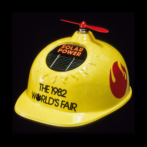 Yellow plastic hard hat with solar-powered propeller on top, souvenir from, Knoxville World's Fair, 1982
