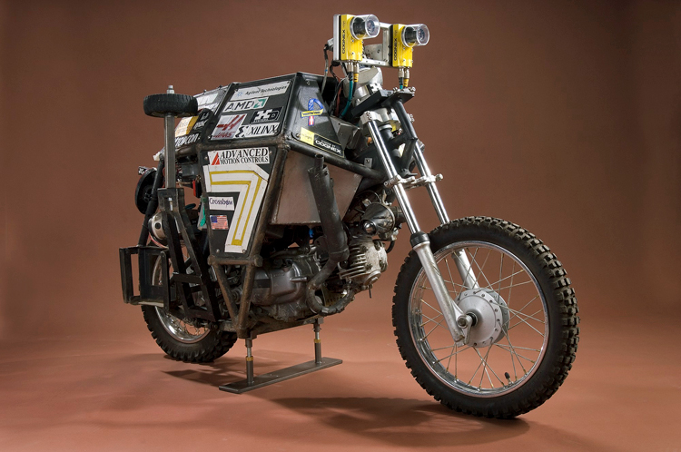 Side view of the Ghostrider autonomous motorcycle. There is a box covering the seat area and it is covered in stickers, including Agilent Technologies and an American flag. Two cameras are located where the handlebars would normally be.