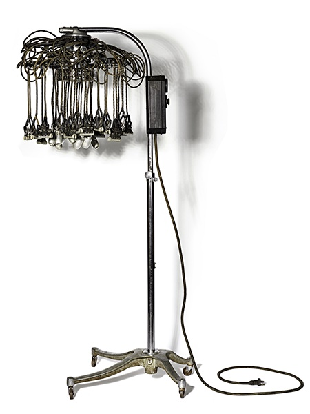 A tall post on a rolling base with multiple wires and rods suspended from a ring at the top