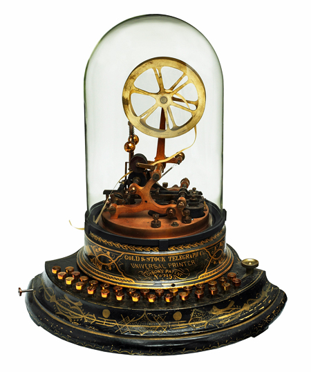 A round metal base with gold ornamentation holds 2 sets of keys, inscribed: Gold & Stock Telegraph Co., Universal Printer, Edison's Patent, No. 215. A metal spool of paper tape sits atop the base and electromechanical contacts, covered by a glass dome.