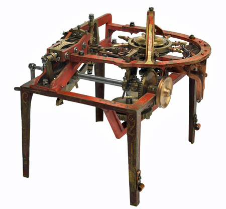 Metal model for a pin-making machine. The legs and open base are painted and ornamented in gold. The mechanism is a complicated arrangement of hand-cranked bevel gears and wire feed for extruding straight pins.