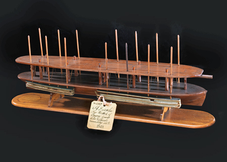 Wooden model of a long, narrow boat hull with air-filled chambers on the outside. The chambers are moved up or down with vertical poles that connect through the hull. Pushing the chambers into the water raises the bottom of the boat.
