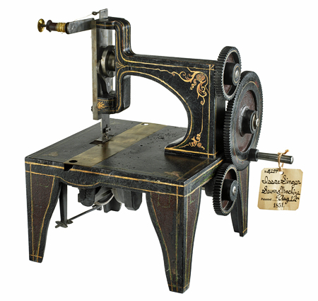 Metal model of Isaac Singer's 1851 sewing machine, with 3 gears on the right and a sewing foot and thread feed on the left. The black metal is ornamented with gold lines and swirling patterns.