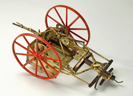 Metal and wood model of a wheeled, horse-drawn device to smooth road surfaces by scraping.