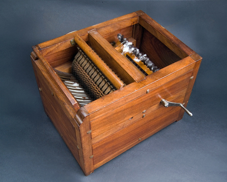 Reproduction wooden box containing several hand-cranked toothed rollers that separate cotton fibers from the seeds. Cleaned cotton fibers are collected in the base of the box.