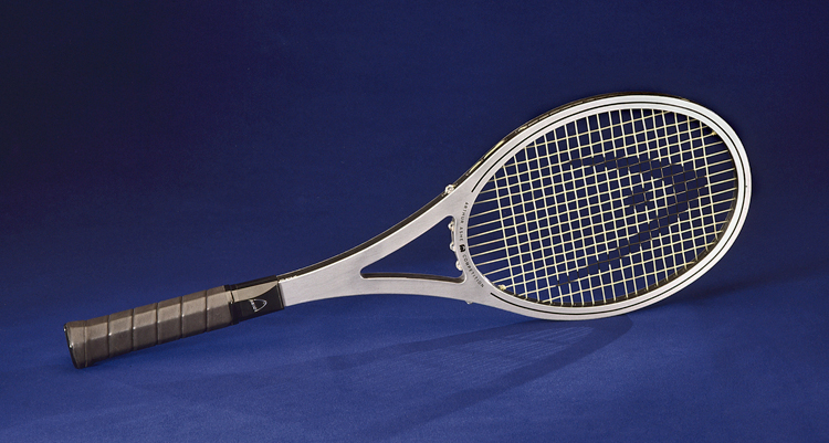 "A silver metal tennis racket with a brown leather-wrapped handle sits on a cobalt blue background. The racket bears the logo of Head tennis rackets on the head and shaft, and the rim reads, ""Arthur Ashe Competition."""