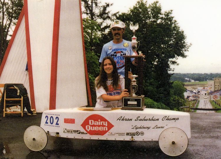14-year-old Laura Shepherd kneels behind her soapbox derby car, holding her trophy, which is resting on the car. Her father stands behind her, with one hand on the trophy. They are at the top of a hill and the soapbox derby downhill course is visible at the right.