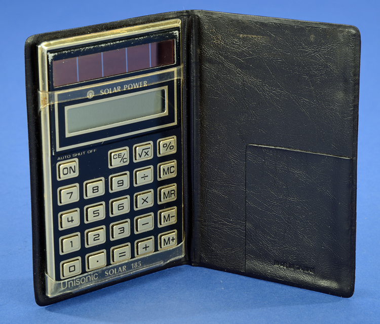 Unisonic Solar 185 handheld electronic calculator in folding pocket case, about 1983. Solar panels are above number display.