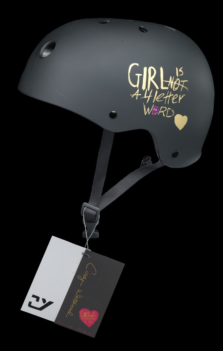 """Skateboard helmet has a black matte finish with """"Girl [/] is [/] NOT [/] A 4 letter [/] Word"""" in gold with a gold heart and a pink skull on the left side of the helmet. """"XS"""" is printed in gold on the front of the helmet. The helmet consists of a black styrofoam core with pink foam inserts and a black nylon chin strap with a black plastic buckle."""