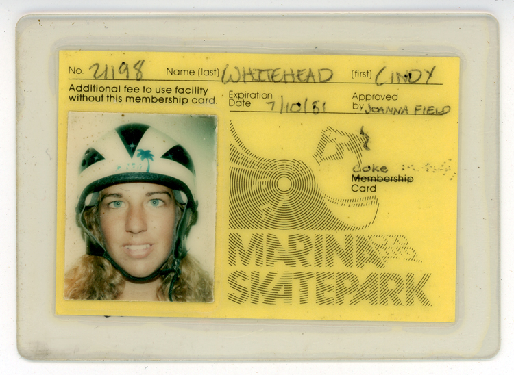 "Laminated identification card for Marina Del Rey Skatepark, with a yellow background, No. 21198, Cindy Whitehead's name, and expiration date of 10 July 1981. A headshot of Whitehead wearing a helmet is on the left of the card; on the right is the name of the park depicted with curving lines suggesting a skate ramp. The word ""membership"" has been crossed out and replaced with the handwritten word ""coke."""