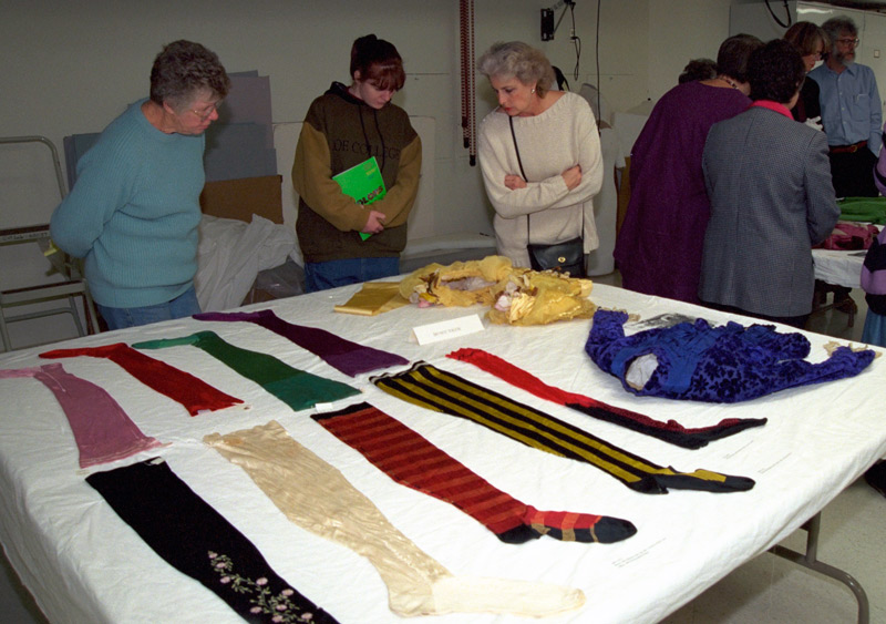 Visitors on a behind the scenes tour during the Color of Invention symposium examine textiles.