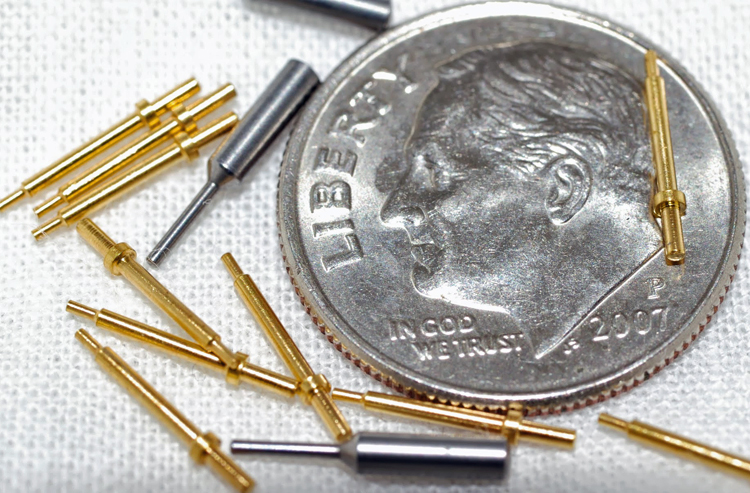 13 small specialty pins made by W.H. Bagshaw Co. in a random arrangement and photographed with a dime for scale