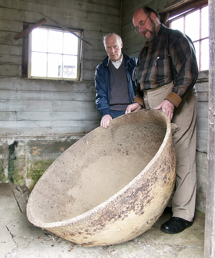 Two men standing, holding a large circular vessel