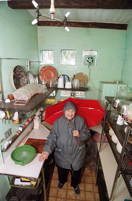 View looking down on Frances Gabe, wearing rain gear and holding an open umbrella, in her self-cleaning house kitchen in 2002