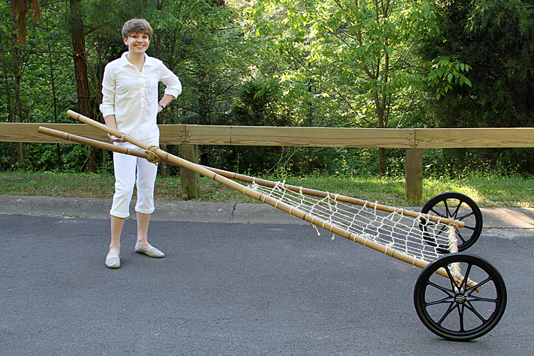 Teenager Alexis Lewis posing with her invention, the Rescue Travois, which is a triangular frame with two wheels on an axle connecting the wide end of the triangle. Netting across the triangle provides a place for passengers and goods to sit.