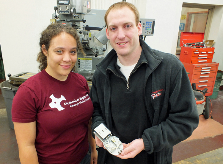 Hahna Alexander (left) and Matthew Stanton posing in a workshop. Stanton is holding their invention, a shoe insole that can store energy created through movement.