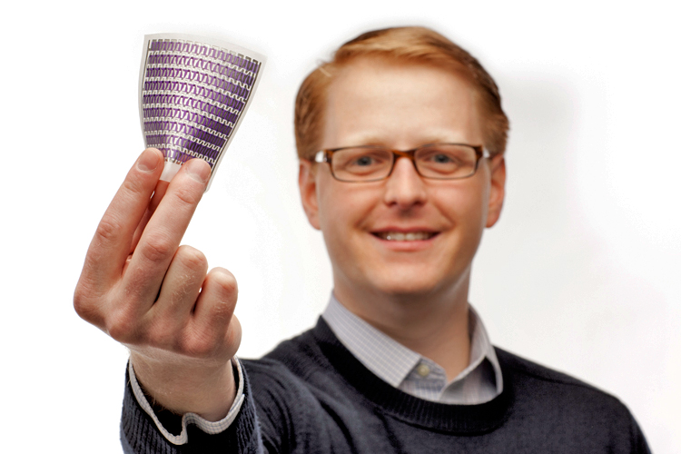 Miles Barr, smiling at camera and holding out a small flexible solar panel that he invented.