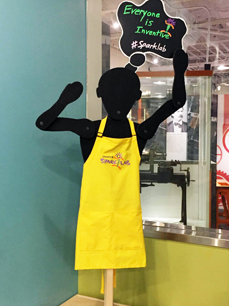 A cut-out silhouette of a man, attached to a post. The figure wears a yellow SparkLab faciliator apron and has a thought bubble above his head that reads Everyone Is Inventive #sparklab
