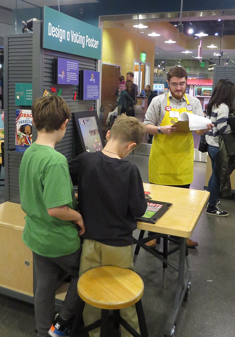 "Two young boys with their backs to the camera work at the ""Design a Voting Poster"" activity table in SparkLab. Lead facilitator Zach Etsch, wearing a yellow SparkLab apron, holds a clipboard and papers used to evaluate the young boys' experience."