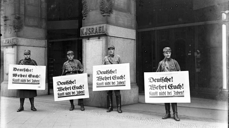 4 Nazi storm troopers holding large signs outside a department store