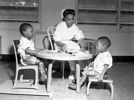 African American nurse sitting at table with two young African American boys who suffer from polio, Tallahassee, Florida, 1953