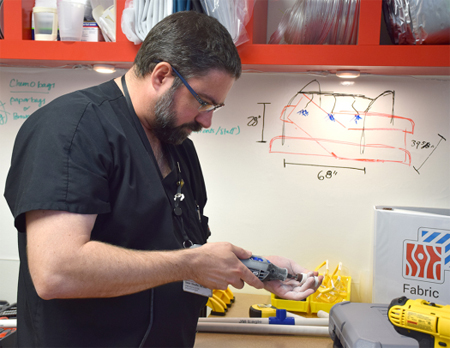 Burn Unit Nurse Manager Jason Sheaffer at a lab bench, working on a prototype of one of his ideas in the MakerHealth Space lab