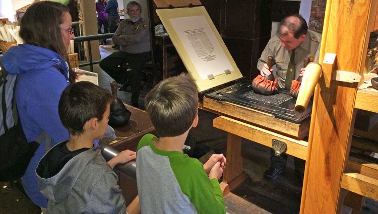 Emma, Gavin, and Patrick Hintz observe National Park Service printing demonstration on a replica of the Franklin printing press