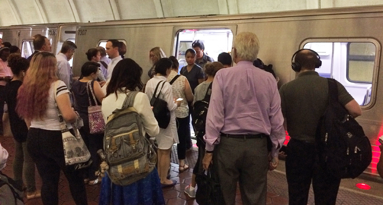 A crowd of people exits a Metro subway car, due to a door malfunction