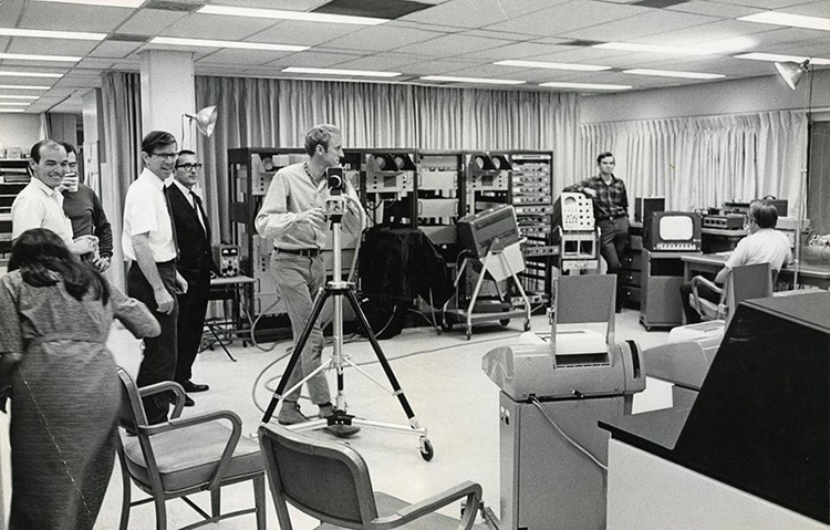 A candid photo of a group of 7 men and 1 woman in a large room filled with computer equipment. A space has been cleared in the center of the room and one of the men, Stewart Brand, is handling a camera on a tripod. 2 studio lights on stands are positioned at opposite sides of the room.