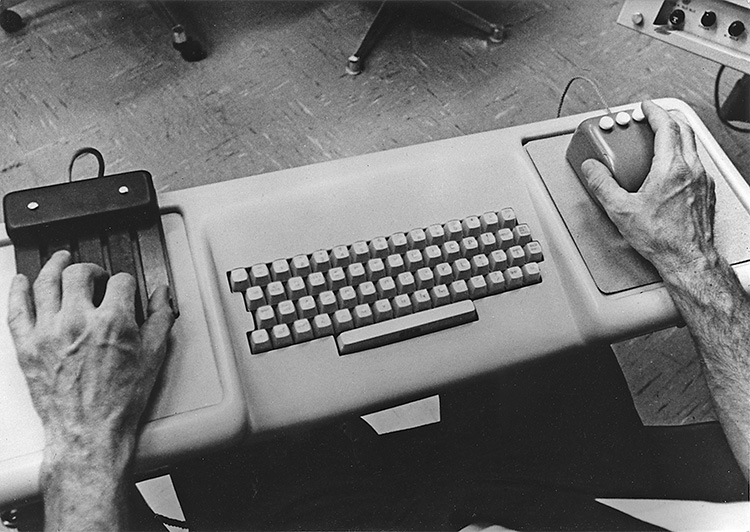 A close-up of Douglas Engelbart's hands. He has his left hand on the NLS 5-button chord keyset, and his right hand holds a 3-button mouse; between the keyset and the mouse is a standard QWERTY keyboard. Platforms for the mouse and keyset are integrated into the keyboard base.