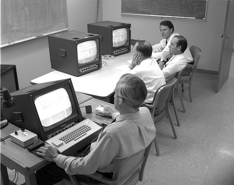 4 men sit at 3 computer terminals. Douglas Engelbart, wearing a wired earpiece, is closest to the camera and is seen in profile. His terminal has a keyboard and he has his hand on a prototype mouse. His computer is linked to the 2 terminals that the other 3 men are watching. Bill English is farthest from the camera.