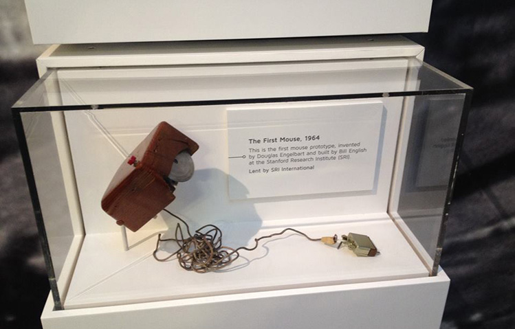 A prototype of the first computer mouse sits on an angled bracket inside a glass display case. The mouse is a dark wooden box with a red button on top. On the underside is a vertical metal wheel. A thin computer cable extends from the back of the mouse.