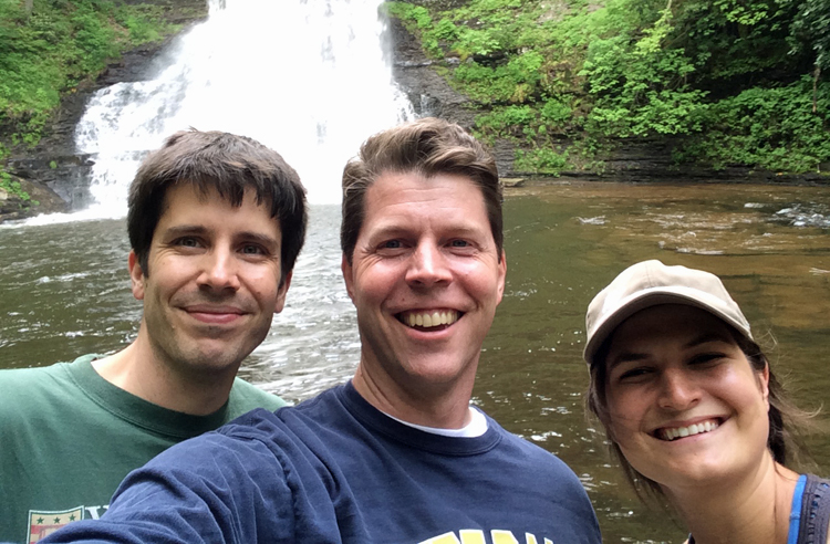 Selfie of (left to right) Matt Wisnioski, Eric Hintz, and Marie Stettler Kleine on the bank of a river with a waterfall in the background.