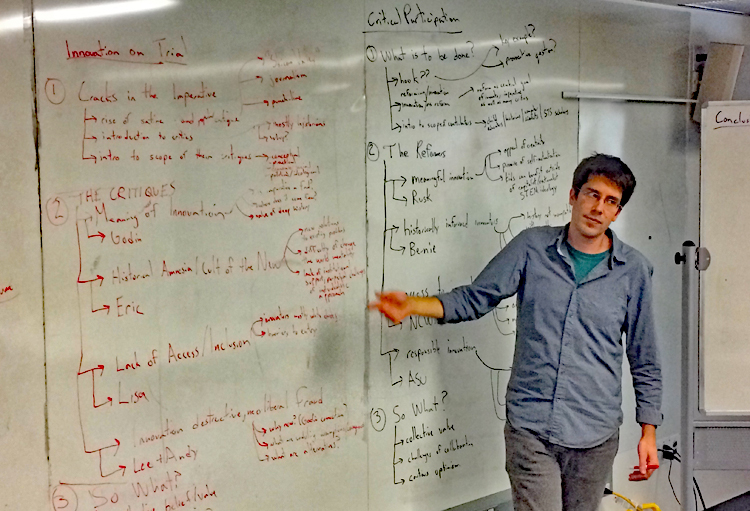 Man pointing at whiteboard covered in writing in red on the left and in black on the right.