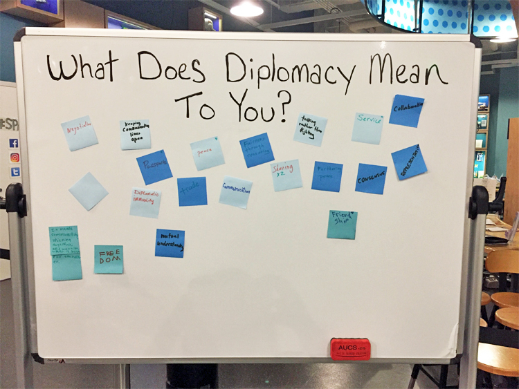 Whiteboard with visitor answers on sticky notes to the question: What does diplomacy mean to you? Answers include negotiation, peace, friendship, and freedom.