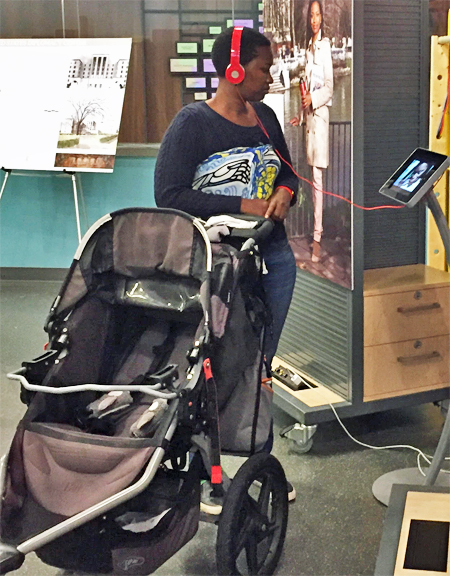 Woman with a stroller listening to a recording of a diplomat