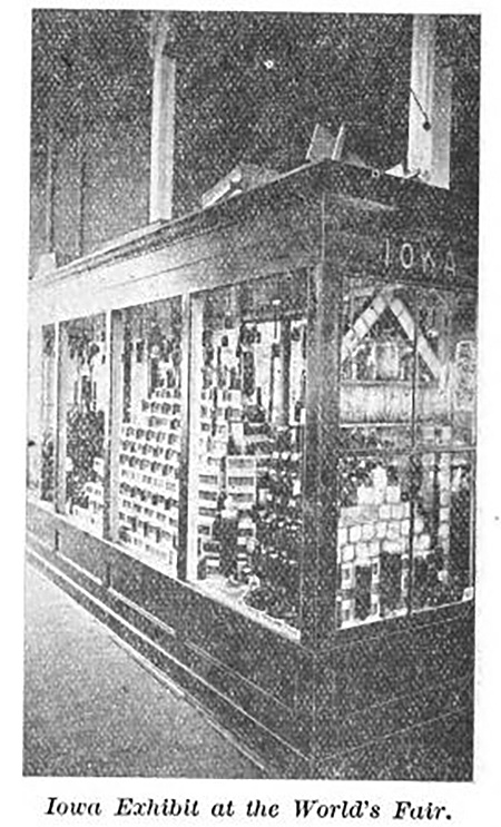 Grainy image of a large glass case holding jars of honey and other products from Iowa