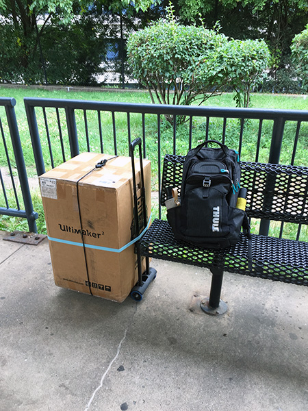 Backpack on a bench next to a box holding a 3D printer