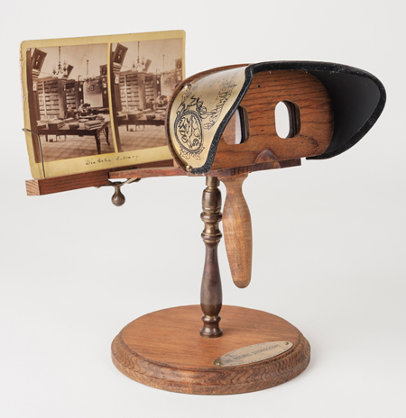 Handheld stereoscope resting on its stand, holding a stereograph. The stereoscope is wood, with an engraved metal visor for shielding the eyes.