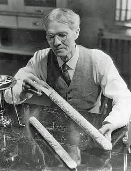 Alexander P. Anderson holding and examining his puffed grain cannon, 1933