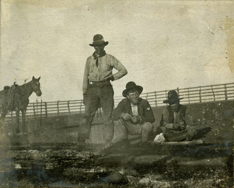 Three cowboys, including one African American cowboy, relaxing in Texas around 1900