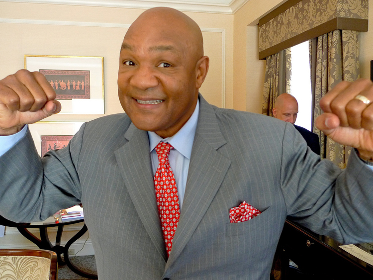 Boxer George Foreman, with arms up and hands clenched as if ready to punch, but with a big grin on his face and wearing a suit