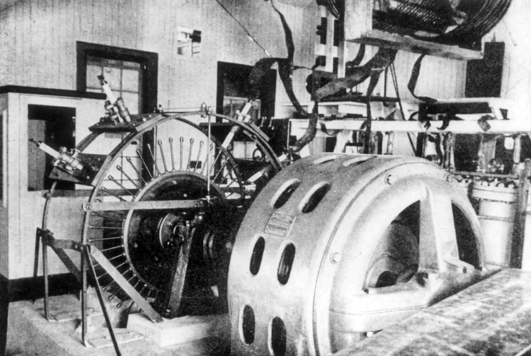 View of Fessenden AC generator and synchronous rotary gap transmitter, showing the drive belt in the foreground, the inductors near the roof, and the high pressure capacitors at the right.