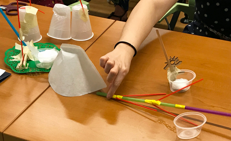 Straws taped together in a straight line, with 4 coffee stirrers attached at 45-degree angles on either side, protrude from under a paper coffee filter. A woman's hand holds the straws in place.
