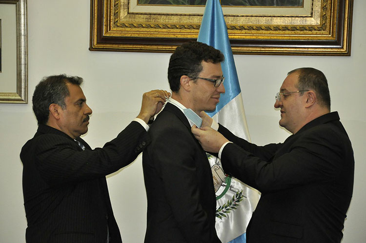 Two men present Luis von Ahn with the Guatemalan government's highest honor, the Order of the Quetzal, by placing it around his neck.