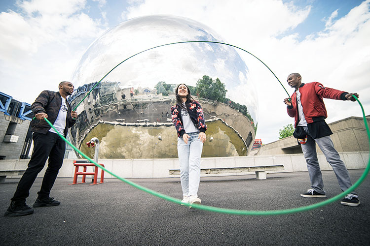 2 men turning the double Dutch ropes while a woman jumps