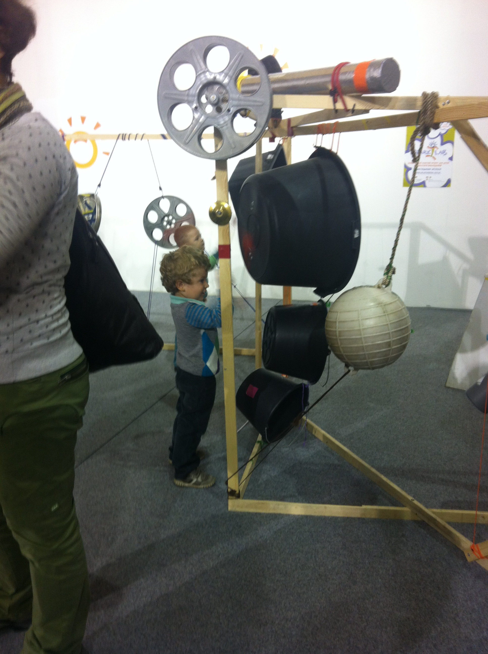 "Boy banging on a buoy that is part of a ""found object"" percussion sculpture"
