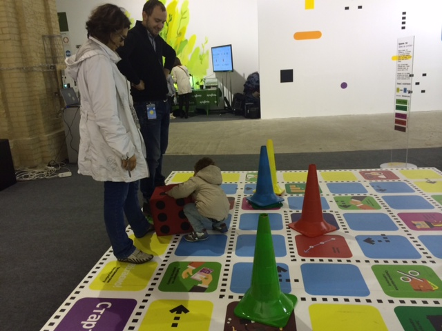 A young visitor plays a board game to learn about money and finances in the Finance Lab