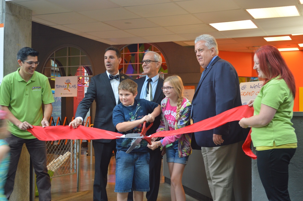 Director Art Molella cuts the ribbon to open Spark!Lab at Science City in Kansas City with representatives from the Museum and the Ford Motor Company Fund, as well as some local children.
